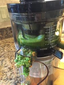 greens being juiced in juicer